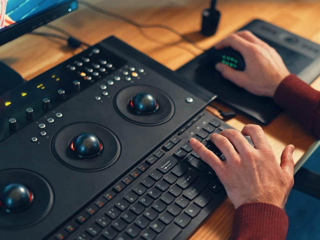 Två händer håller på med en manöverpanel med knappar och reglage som styr arbetet av videoredigering